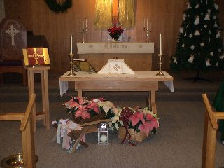 Left: A recent years' tradition of poinsettias to remember those loved ones from christmases past, and in front the rickety  creche readied with cloth strips for the baby Jesus