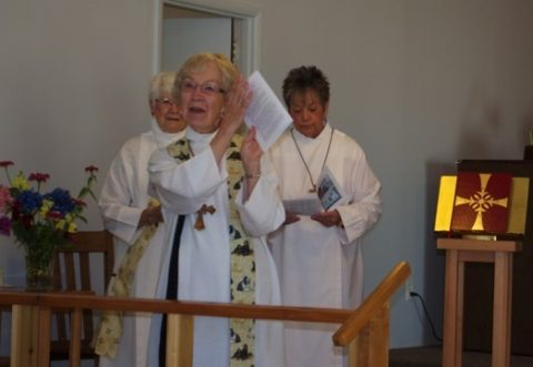 Rev. Lorraine Dierick shows everyone the worship program to be used for the service.